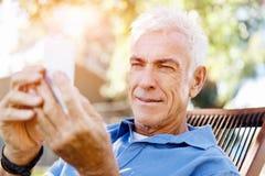 Человек LoMature outdoors используя мобильный телефон стоковые изображения rf