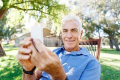 Человек LoMature outdoors используя мобильный телефон стоковая фотография rf