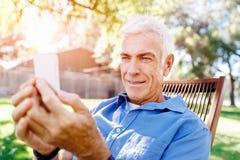 Человек LoMature outdoors используя мобильный телефон стоковое изображение