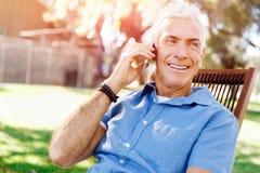 Человек LoMature outdoors используя мобильный телефон стоковые фото