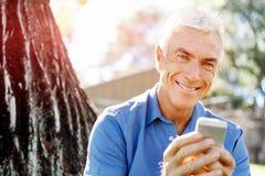 Человек LoMature outdoors используя мобильный телефон стоковая фотография