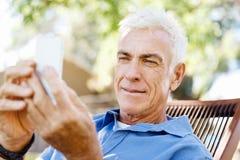 Человек LoMature outdoors используя мобильный телефон стоковые изображения