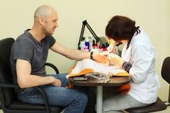 Человек manicure женщины специальными схватами Стоковая Фотография
