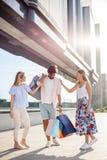 Человек Oung нося все сумки пока 2 девушки смеющся и шутящ его стороной стоковые фото