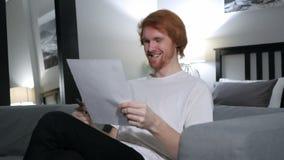 Человек Redhead возбужденный после читать документы сток-видео