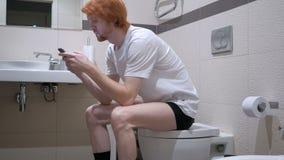Человек Redhead используя Smartphone в туалете, Commode акции видеоматериалы