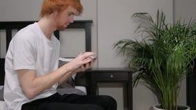 Человек Redhead сидя на стороне кровати используя телефон для интернета видеоматериал