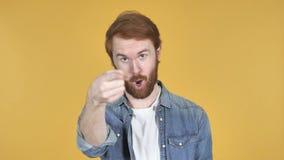 Человек Redhead указывая на камеру, желтую предпосылку
