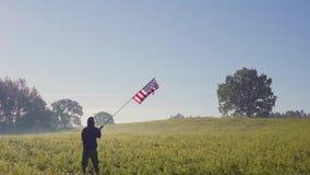Человек, silhouetted, освещенный солнцем, стойки на валуне, держит американский флаг который развевает акции видеоматериалы