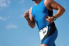 Человек triathlete бегуна триатлона бежать в tri костюме на гонке конкуренции ironman Стоковое фото RF