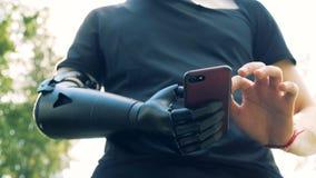 Человек Yong с искусственной рукой используя smartphone Будущая принципиальная схема