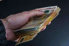Человеческая рука держа банкноты деньг-евро изолированный на темноте - серой предпосылке Стоковые Фотографии RF