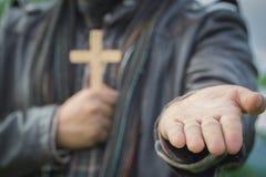 Человеческая рука держит крест и открытая ладонь вверх поклоняется Евхаристия Thera стоковое фото