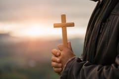 Человеческая рука держит крест Терапия евхаристии благословляет бога помогая Rep стоковые фотографии rf