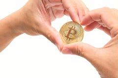 Человеческая рука ` s формируя символ сердца против bitcoin cryptocurrency золотого на белизне изолировала предпосылку Виртуально Стоковые Фото