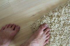 Человеческие босые ноги стоя на поле Одна нога на ковре и Стоковые Изображения RF