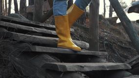 Человеческие ноги в желтых резиновых ботинках и голубых джинсах идут вниз на деревянные лестницы outdoors Ноги в приходить резино видеоматериал