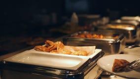 Человеческие руки кладя на еду плиты от таблицы шведского стола в конец ресторана гостиницы вверх сток-видео