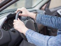 Человеческие руки на руле, внутри взгляда кабины, конец вверх, выборочный фокус Обычный человек управляя автомобилем стоковые фотографии rf