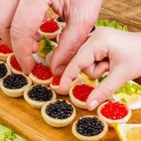 Человеческие руки принимают tartlets с красной и черной икрой Еда Backgr Стоковые Изображения