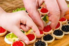 Человеческие руки принимают tartlets с красной и черной икрой Еда Backgr Стоковое Изображение RF