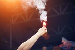 Человеческий на рок-концерте поднял руку в верхней части красного огня стоковое изображение rf