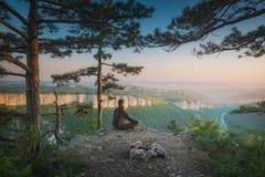 Человеческое усаживание в представлении йоги на край скалы стоковое изображение rf