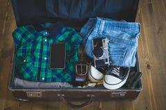 Чемодан винтажной упаковки путешественника битника открытый на деревянной доске с одеждой, фильм-камерой и чернью Стоковое Изображение RF