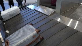 Чемодан двигает дальше конвейерную ленту багажа в крупном аэропорте видеоматериал