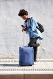Чемодан счастливой молодой женщины готовя смотря мобильный телефон Стоковое Фото