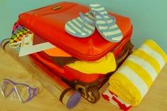 Чемодан с вещами для проводить летние каникулы Превидение рейса Одежды и аксессуары ` s женщин в чемодане Стоковые Изображения RF