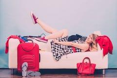 Чемодан упаковки молодой женщины на софе Стоковая Фотография