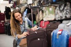 Чемодан девушки покупая в магазине Стоковые Изображения