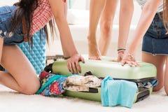 Чемодан женщин пакуя на каникулы совместно дома, пакуя концепцию багажа Стоковое фото RF