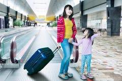 Чемодан нося матери и дочери на авиапорте Стоковые Фото