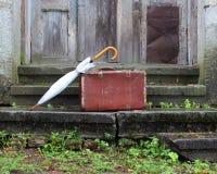 Чемодан старый и зонтик на крылечке Стоковая Фотография RF