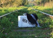 Чемодан старый с надписью НЬЮ-ЙОРКОМ на железнодорожных путях Стоковые Фотографии RF