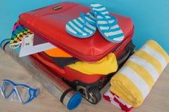 Чемодан с вещами для проводить летние каникулы Превидение рейса Одежды и аксессуары ` s женщин в чемодане Стоковое фото RF