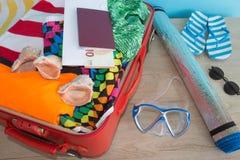 Чемодан с вещами для проводить летние каникулы Превидение рейса Одежды и аксессуары ` s женщин в чемодане Стоковое Изображение RF