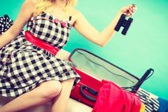 Чемодан упаковки молодой женщины на кресле Стоковые Изображения