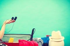 Чемодан упаковки молодой женщины на кресле Стоковые Фото