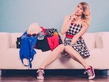 Чемодан упаковки молодой женщины на софе Стоковые Изображения