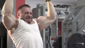 Чемпион культуризма делая трудную тренировку для оружий и плеч медленно сток-видео