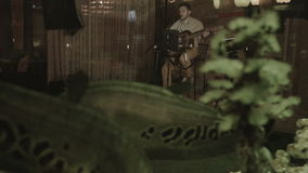 Через аквариум с рыбами, музыкант играет на этапе ` s ресторана сток-видео