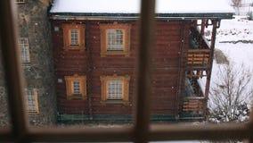 Через взгляд окна деревянного коттеджа в горном селе во время сильного снегопада Снег падая на шале журнала с сток-видео