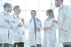 Через стекло группа в составе доктора стоя в офисе Стоковая Фотография RF