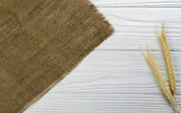 Черенок пшеницы и ткань hessian на белой деревянной предпосылке стоковое изображение rf