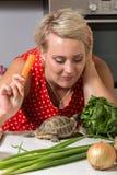 Черепаха есть римский салат пока молодая женщина жует морковь Стоковое Фото