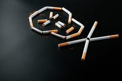 Череп от сигарет на черной предпосылке Концепция куря убийств К концепции курения как смертельная привычка, стоковые изображения rf