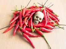 Череп с красными chilies на деревянной плите Стоковая Фотография